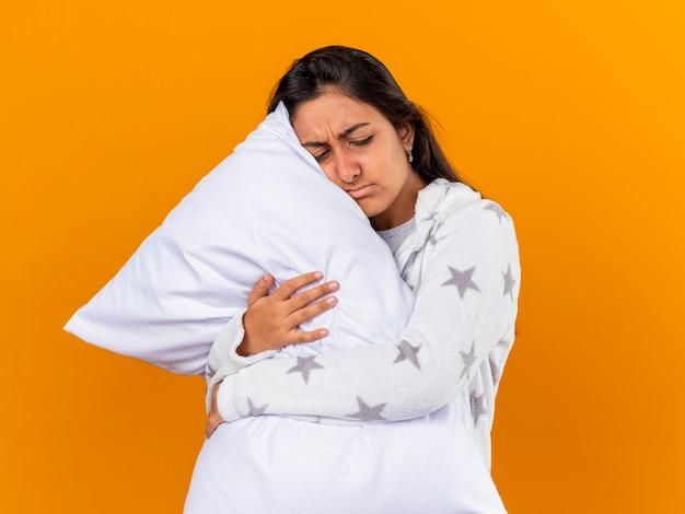 目を閉じて悲しい若い病気の女の子は黄色で隔離の枕を抱きしめた
