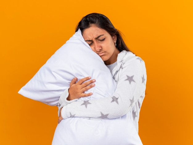 Sad young ill girl with closed eyes hugged pillow isolated on yellow