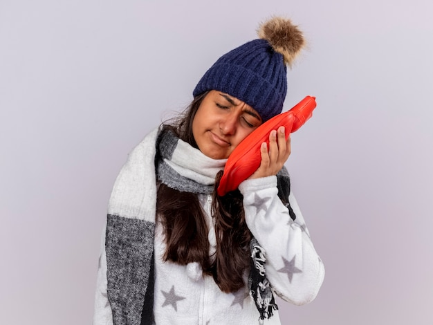Sad young ill girl with closed eyes wearing winter hat with scarf putting hot water bag on cheek isolated on white background