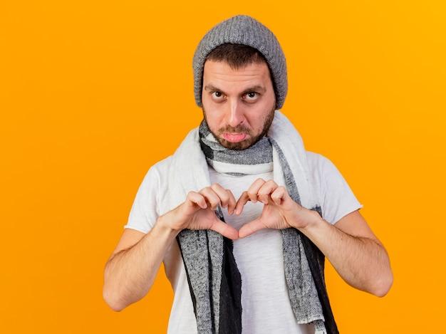Triste giovane uomo malato che indossa un cappello invernale e sciarpa che mostra il gesto del cuore isolato su sfondo giallo