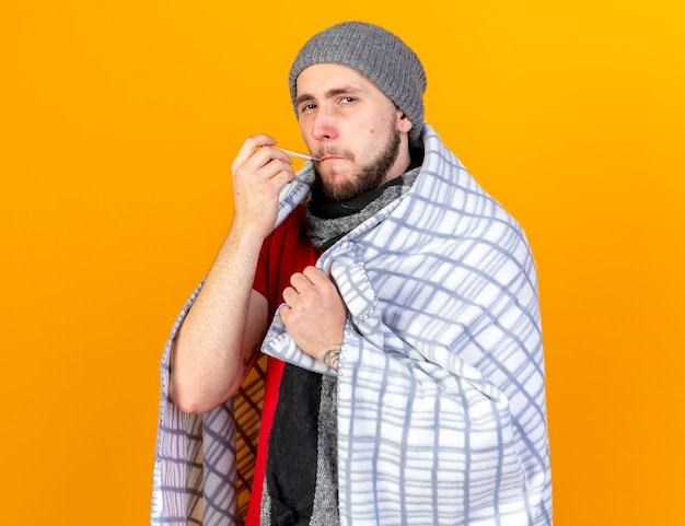 Sad young ill man wearing winter hat and scarf wrapped in plaid keeps thermometer in mouth isolated on orange wall