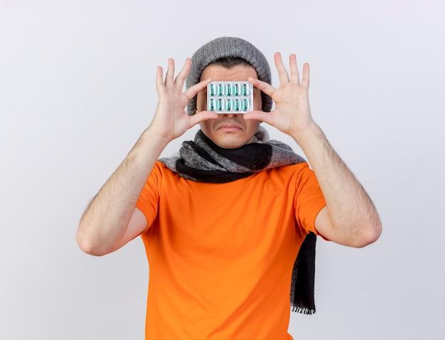白で隔離の丸薬でスカーフで覆われた顔と冬の帽子をかぶって悲しい若い病気の男