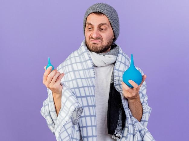 Triste giovane uomo malato che indossa cappello invernale con sciarpa che tiene e guardando clistere isolato su sfondo viola