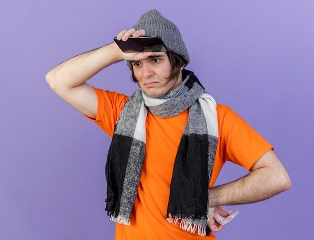 Грустный молодой больной человек в зимней шапке с шарфом держит телефон, положив руки на лоб и бедро, изолированные на фиолетовом