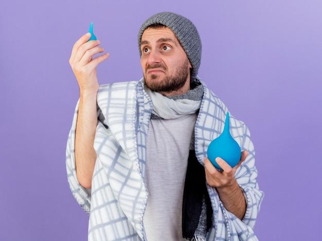 Triste giovane uomo malato che indossa cappello invernale con sciarpa alzando e guardando clistere isolato su sfondo viola