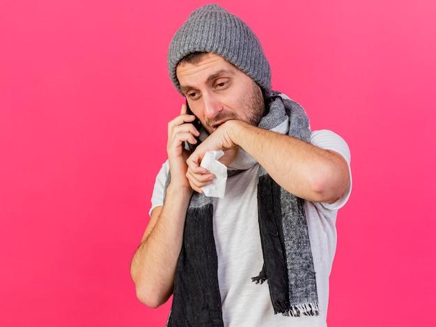 スカーフと冬の帽子をかぶって悲しい若い病気の男は、ピンクの背景で隔離の手でナプキンとあごを拭いて電話で話します