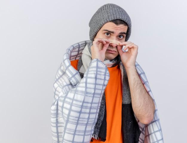 白で隔離の鼻に石膏を置く格子縞に包まれたスカーフと冬の帽子をかぶって悲しい若い病気の男