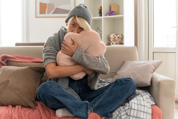 Triste giovane donna slava malata con sciarpa intorno al collo che indossa cappello invernale abbracciando cuscino seduto sul divano in soggiorno