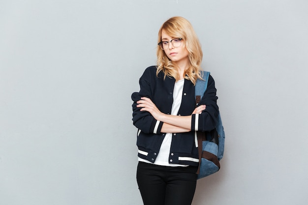 Sad young lady student wearing glasses with backpack