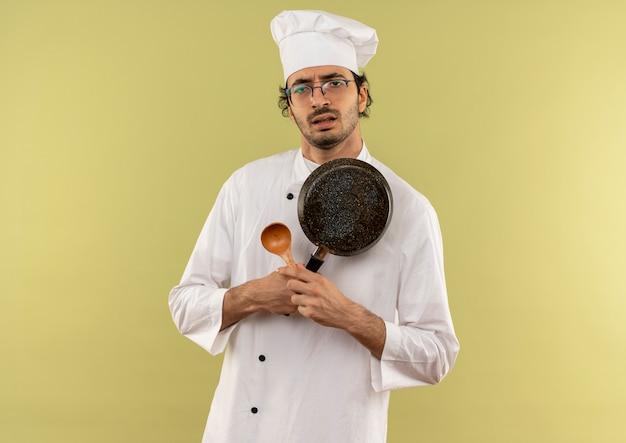 요리사 유니폼과 안경을 들고 숟가락으로 프라이팬을 건너는 슬픈 젊은 남성 요리사