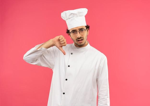 Triste giovane cuoco maschio indossa uniforme da chef e occhiali con il pollice verso il basso