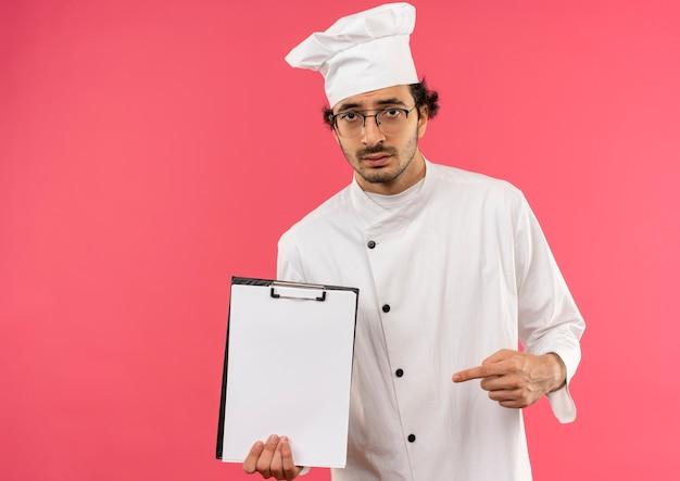 Triste giovane cuoco maschio che indossa l'uniforme dello chef e bicchieri tenendo e punta a clipbord