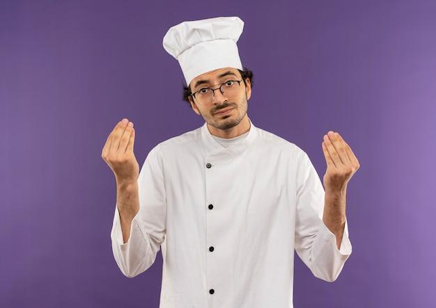 Triste giovane cuoco maschio che indossa l'uniforme dello chef e bicchieri che mostrano il gesto di punta