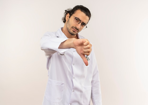 聴診器と彼の親指を下に白いローブを着て光学眼鏡をかけた悲しい若い男性医師