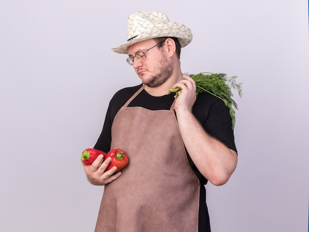 Sad young male gardener wearing gardening hat holding peppers with dill isolated on white wall