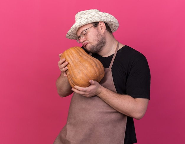 Sad young male gardener wearing gardening hat hugged pumpkin isolated on pink wall