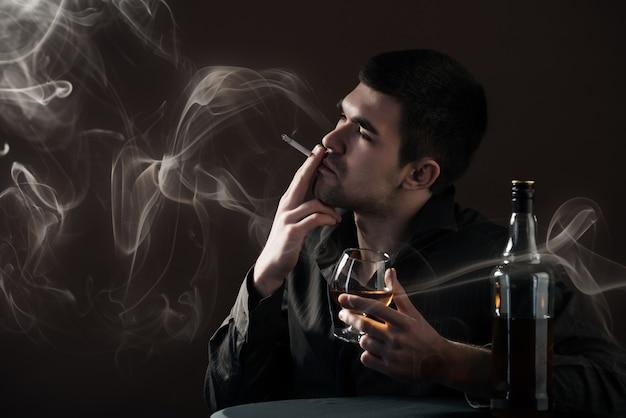 슬픈 젊은 남자는 검은 배경에 어두운 방에 앉아 닭에서 알코올 음료를 친다.