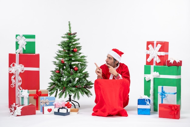 Sad young man dressed as santa claus with gifts and decorated christmas tree pointing something on the right side on white background