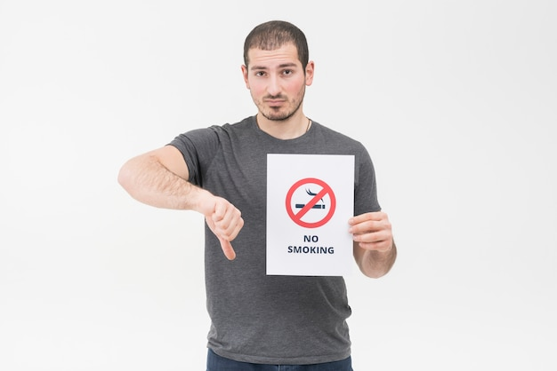 Sad young man holding no smoking sign showing thumb down gesture against white background