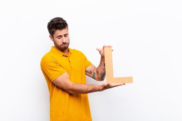 Грустный молодой человек, держащий букву l