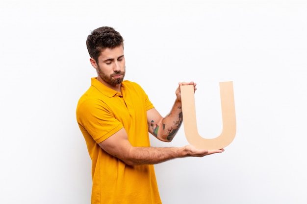 Грустный молодой человек, держащий букву u