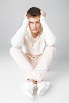 Грустный молодой человек в белом свитере сидит на полу, много проблем или головная боль