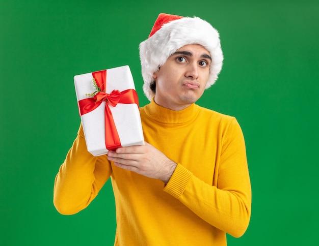 Грустный молодой человек в желтой водолазке и шляпе санта-клауса показывает подарок, глядя в камеру, поджимая губы, стоя на зеленом фоне