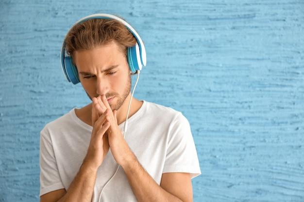 色の表面で音楽を聴いている悲しい若者