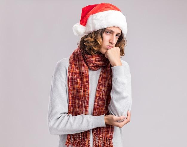Giovane triste che indossa il cappello di babbo natale con una sciarpa calda intorno al collo con la mano sul mento pensando in piedi sul muro bianco