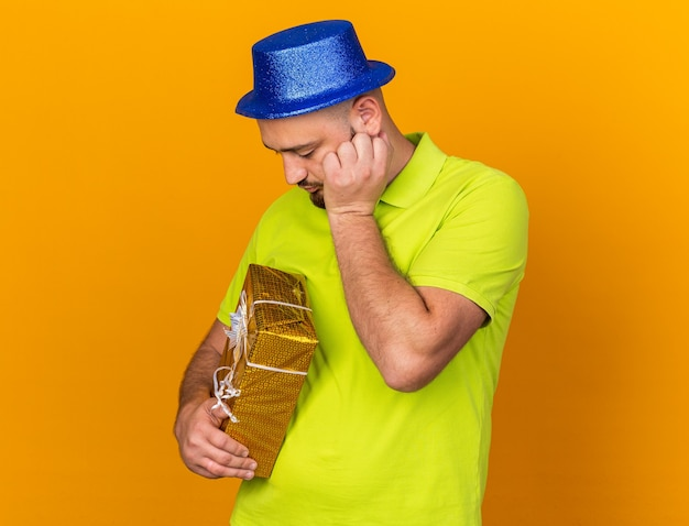 Sad young man wearing party hat holding gift box putting hand fist on cheek