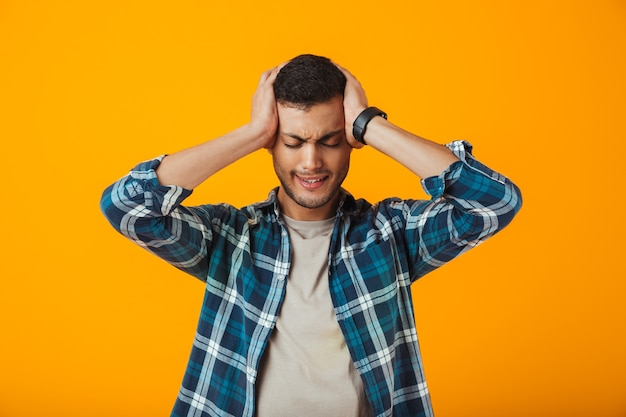 Sad young man wearing plaid shirt standing isolated over orange wall, suffering from a headache