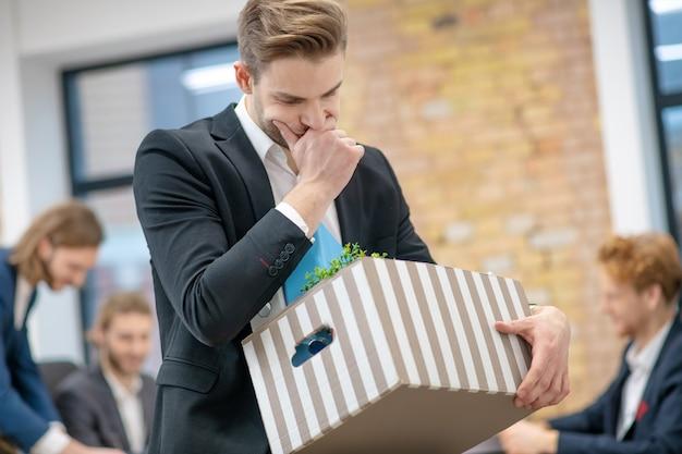 物思いにふける私物の箱を持った悲しい青年が孤立し、同僚がオフィスにいる