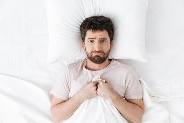 Sad young man with headache in the morning under blanket in bed