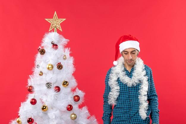 Giovane triste con il cappello di babbo natale in una maglietta spogliata blu e guardando in basso in piedi vicino all'albero di natale sul rosso
