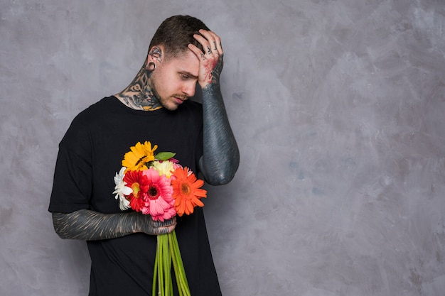 Sad young man with tattoo on his body holding fresh colorful gerbera flowers
