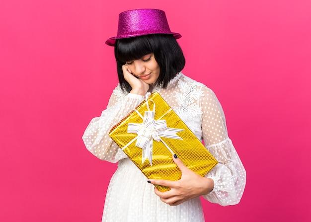복사 공간이 있는 분홍색 벽에 격리된 닫힌 눈으로 얼굴에 손을 대고 선물 꾸러미를 들고 파티 모자를 쓴 슬픈 젊은 파티 소녀