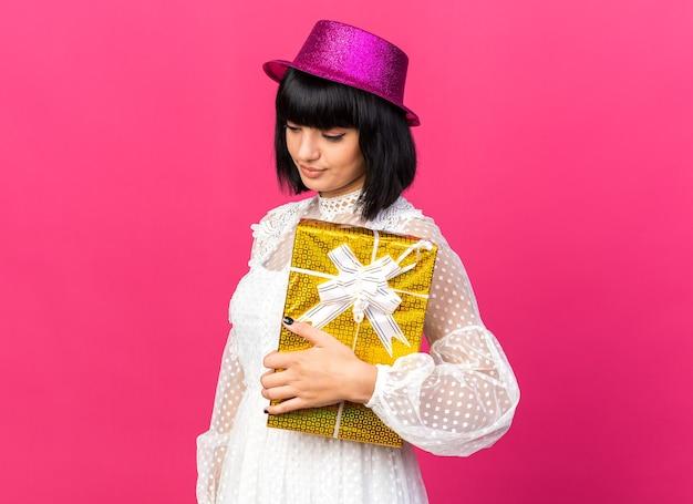 프로필 보기에 서 있는 파티 모자를 쓴 슬픈 젊은 파티 소녀는 복사 공간이 있는 분홍색 벽에 격리된 아래를 내려다보는 선물 패키지를 들고 있습니다