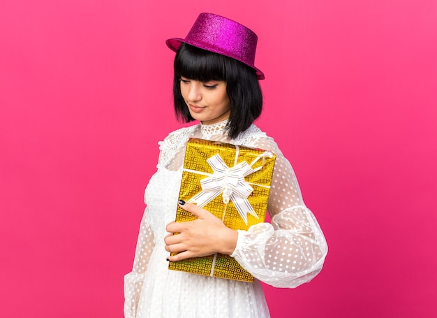 Sad young party girl wearing party hat standing in profile view holding gift package looking down isolated on pink wall with copy space