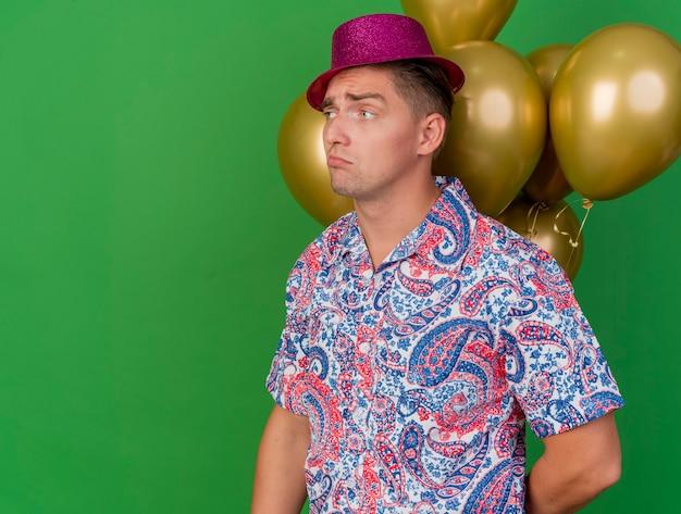 緑に分離された風船の前に立っているピンクの帽子をかぶって側を見て悲しい若いパーティー男