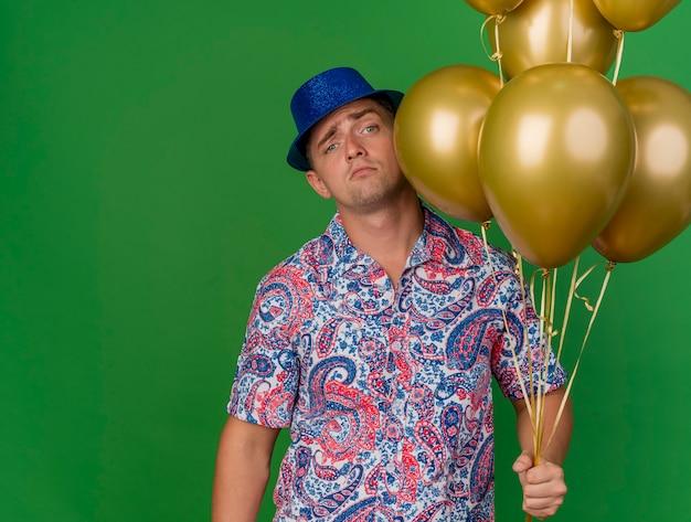 복사 공간이 녹색 배경에 고립 된 풍선을 들고 파란색 모자를 쓰고 슬픈 젊은 파티 남자