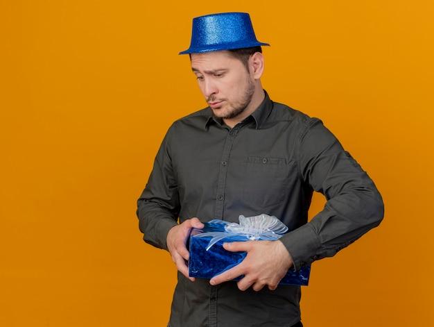 Ragazzo triste del partito giovane che indossa il cappello blu che tiene il contenitore di regalo isolato sull'arancio