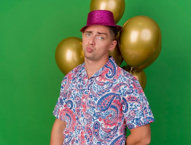 緑で隔離の風船の前に立っているピンクの帽子をかぶって悲しい若いパーティー男