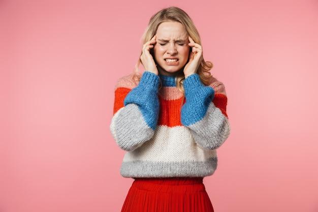ピンクの壁に孤立したポーズの頭痛の悲しい若いかなり美しい女性