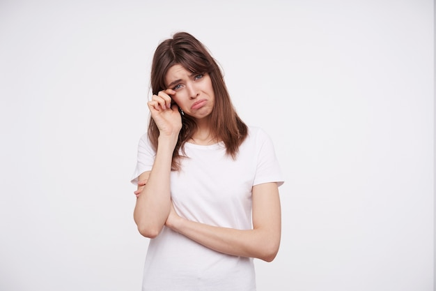 Sad young pretty brunette woman with natural makeup twisting drearily her mouth and raising hand to her eye while looking  with upset face, standing against white wall