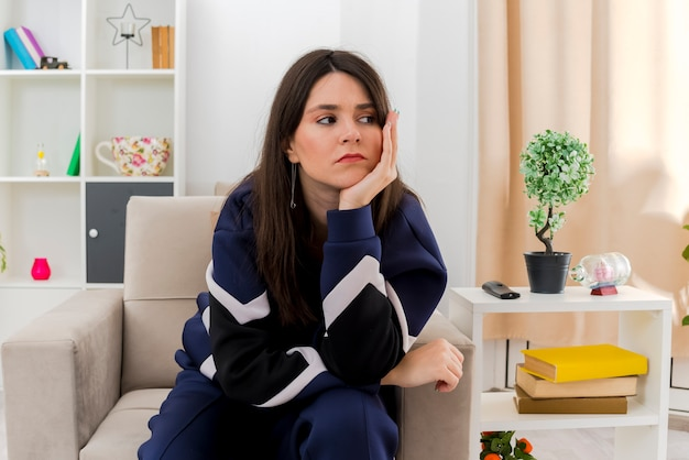 Sad young pretty caucasian girl sitting on armchair in designed living room looking at side and putting hand under chin
