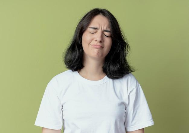 Грустная молодая красивая кавказская девушка с закрытыми глазами на оливково-зеленом фоне