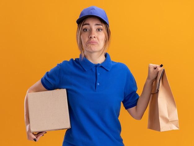 Sad young pretty delivery girl in uniform holds paper package and cardbox on orange