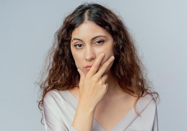Impiegato di ufficio femminile abbastanza giovane triste che mette la mano sulla bocca isolata su bianco
