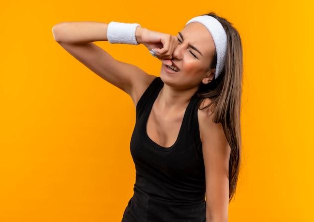 Triste giovane ragazza abbastanza sportiva che indossa la fascia e il braccialetto che grida mettendo la mano sul viso con gli occhi chiusi isolati su spazio arancione