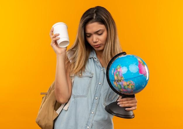 Грустная молодая симпатичная студентка в сумке на спине, держащая пластиковую кофейную чашку и глобус, смотрящую вниз, изолированную на оранжевой стене